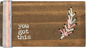 "Wooden block featuring ""You Got This"" sentiment with hand-stitched feather design and layered vertical border detail. Contains strong back magnet or can free-stand alone."