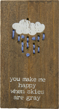 """A wooden block featuring """"You Make Me Happy When Skies Are Gray"""" sentiment, cloud design, and hand-stitched raindrop accents. Contains strong back magnet or can free-stand alone."""
