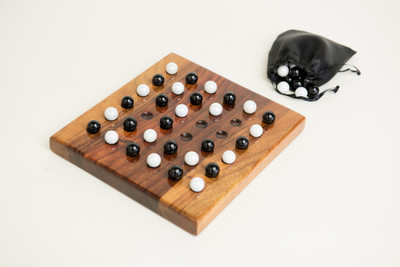 Small konane board, shown with game pieces