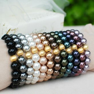 Pearl Stretch Bracelets shown in (left to right) Mystic Black, Dark Gray, White, Powder Almond, Bronze, Brown, Dark Green, Tahitian-Look, Dark Purple, Burgundy, Mauve.