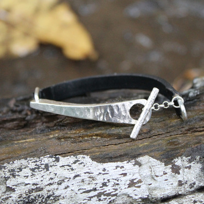 Black thin leather bracelet with silver detail and toggle closure