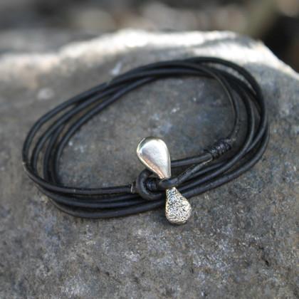 White bronze toggle closure on black multi wrap leather bracelet