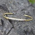"Silver and brass adjustable bracelet features ""live simply"" message"