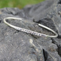 "Silver adjustable bracelet features ""wanderlust"" message"