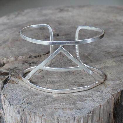 silver statement cuff featuring Explore glyph symbol