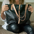 minimalist black leather tote with natural leather straps and closure