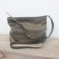 grey leather handbag with top zipper and adjustable straps