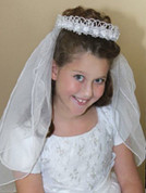 First Communion Veil with Bow Style headpiece embellished with Flowers and Pearls has Two-Tiered tulle veil with finished edge measures22 inches ZCV821
