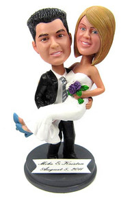 Groom carrying his bride custom wedding cake topper