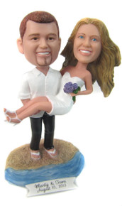 Groom carrying his bride at the beach wedding cake topper