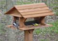A downy woodpecker and a goldfinch come to feed at the Super Feeder.
