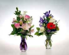These modern vases are designed with seasonal flowers such as Blue Iris, Gerber Daiseys, colorful long lasting Roses and aromatic stock