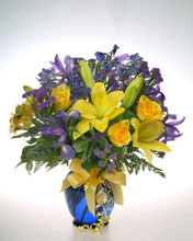 The Joseph-Beth Booksellers signature vase. This cobalt blue glass vase is filled with blue iris, yellow roses and yellow day lillies.