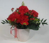 Red carnations in golf ball mug