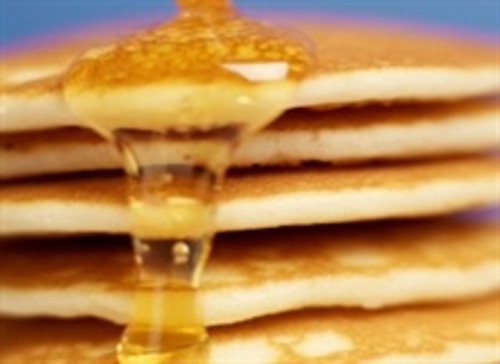 Stack of pancakes with a thick drizzle of maple syrup