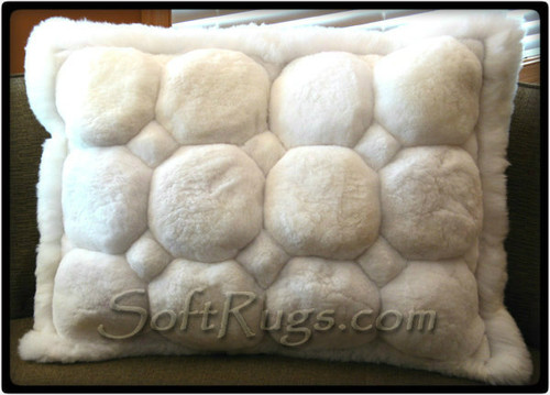 Alpaca Throw Pillow with White Puffs. This pillow features octogonal accents and has a white border.