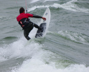 Cresting a wave with the kiteboard's nose up