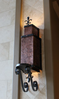 copper lighting sconce with a scrolled base and candle shelf