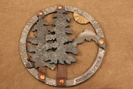 hand-hammered iron trivet with trees, mountain and sun
