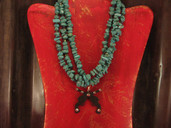 Triple strand turquoise necklace with crossed pistol pendant