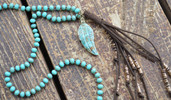 Long turquoise knotted bead necklace with feather pendant and suede tassel