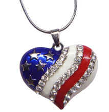 Heart shaped patriotic pendant with silver-plate stars on a blue background. Diamond-like crystals decorate a white background and a red enamel stripe. Front view.