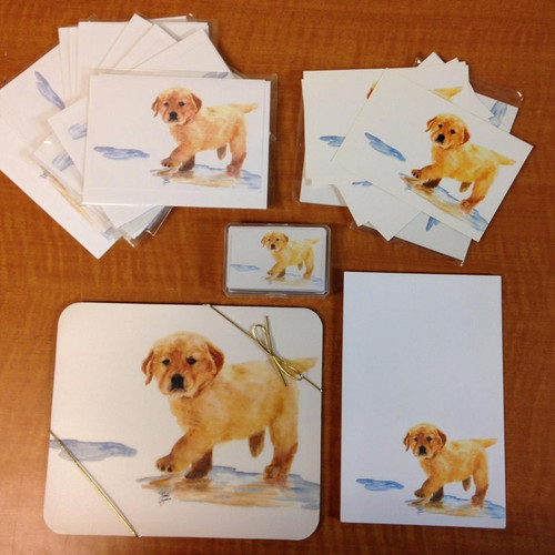 """The Puddles Package makes the perfect gift for any golden retriever lover. The Puddles design featured here is an original watercolor from Denver artist Jody O'Meara. Meant to capture the golden retriever spirit and brighten the world a little at the same time, this beautiful watercolor puppy is sure to bring a smile to your face.  The Puddles Package includes: ◦10 greeting cards (& envelopes) with Puddles on the cover of the card. The inside of the cards say, """"What the world needs now is more unconditional love."""" ◦1 Puddles Note Pad ◦25 Blank Puddles Greeting Cards ◦1 Deck of Puddles Playing Cards ◦1 Puddles Mouse Pad"""