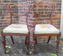 Pair of antique English side chairs with carved back stretcher and original needlepoint seat covers.