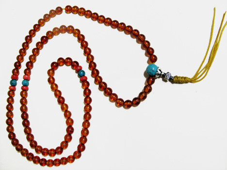 Amber mala with natural, fine-quality 7mm beads and red coral resting bead spacer and Turquoise bead spacers. Capped  with a Turquoise guru bead capped in silver.