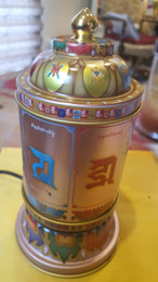 Love and compassion electric prayer wheel with Om Mani Padme Hum, side view with seed syllable mantra.