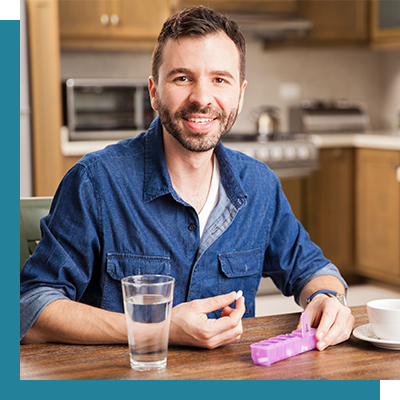 Image of a man in his kitchen taking medicine.