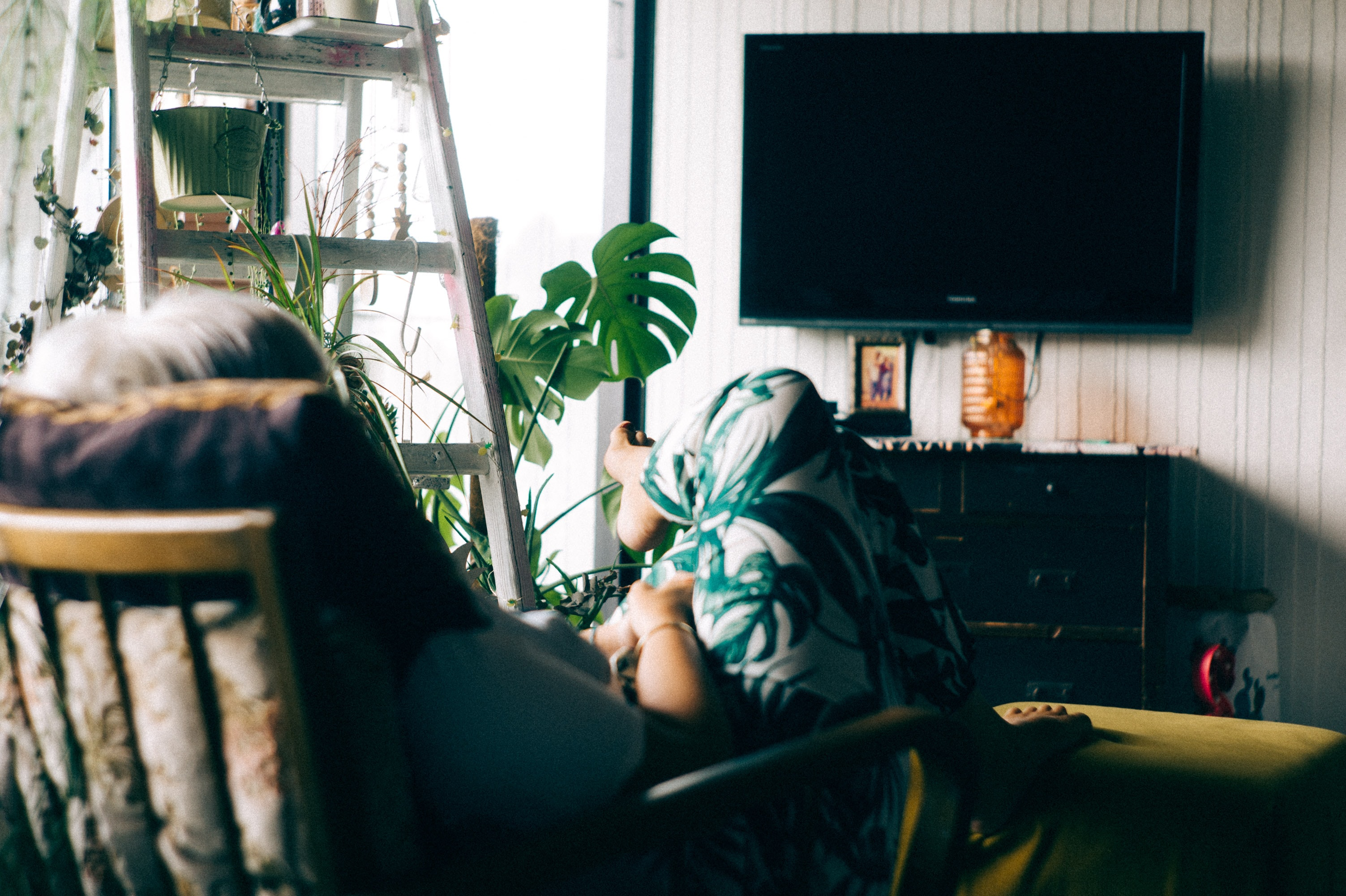 A woman relaxing while effortlessly meditating in front of a television.