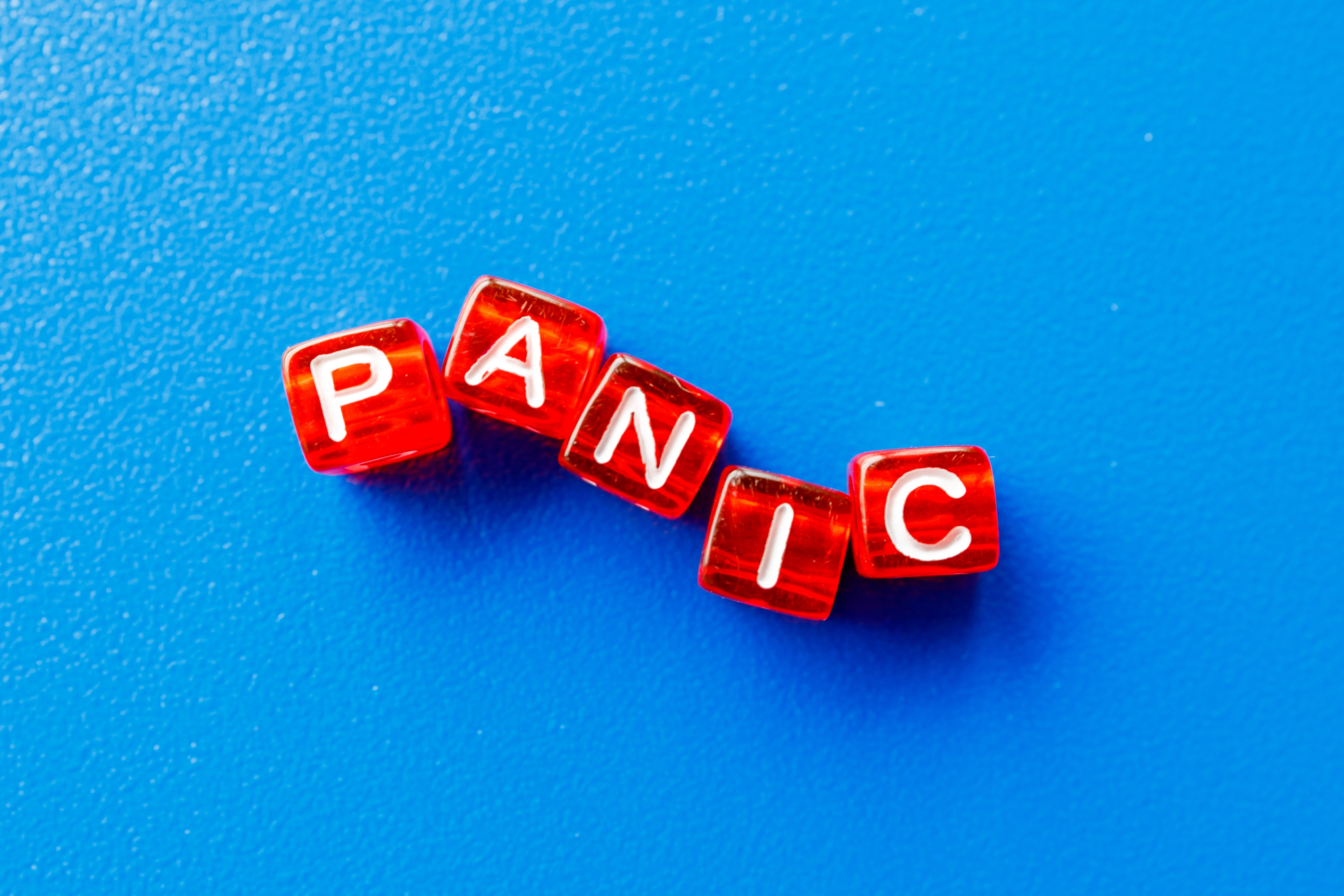 Red dice with the words panic on them laying on a blue background.