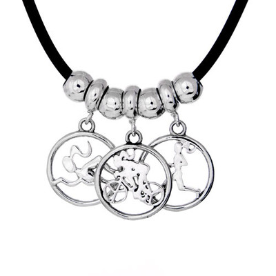 3 circle cutout charms on a black cord necklace with sterling silver spacer beads. Each charm is on a dainty charm carrier.