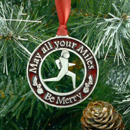 Red round pewter christmas ornament with saying May all Your Miles be Merry hanging on a tree.