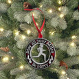 Red pewter christmas ornament with saying May all Your Miles be Merry hanging on a tree with lights.