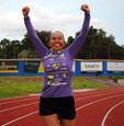 Model running with hands up in the purple triathlon hoodie.