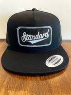 Trucker hat in all black with a black/white/grey the Genuine logo patch.