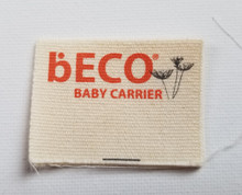 """Micro organic printed cotton label in center fold with fold above the logo so it can be inserted into a seam for sewing. Size is 1.75"""" x 1.25"""" folded."""