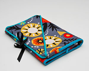 judipatuti's Take Along design provides two convenient pockets that are zipped in one contrasting color!  A different, but complimentary, print lines the inside.  Use it to carry your tools on one side and project and beads on the other.  When it's full just fold it in half and tie with the attached ribbons or lay it flat in your Tote Bag.  This little Take Along will serve you well in your studio and when traveling to your favorite beading or sewing retreats!  They also make great gifts! Fiesta Take Along will receive many comments from your friends!