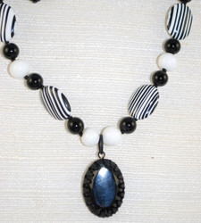 Close up view of Jet Glass Oval Pendant w/matte black metal and beads