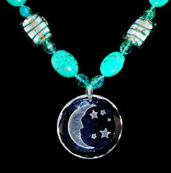 Close up of beads and moon and stars glass pendant