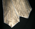 """11"""" X 94"""" light weight striped table runner in shades of golds and silvers with an iridescent sheen.  The table runner has a silver satin edging."""