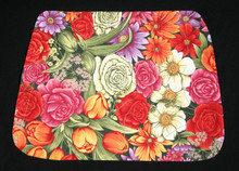 """16"""" X 11 1/2"""" Bright colored floral place mat. Shaped wider at the bottom to use on a round table.  Light weight cotton fabric with white light weight cotton backing.    Washable."""