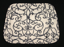 """17"""" X 12 1/2"""" Tan with black swirl design placemat.  Self fabric bias edging.  Medium weight fabric with medium weight interlining and black fabric backing.  Shaped wider at the bottom to use on a round table. Washable in cold water."""