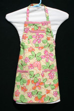 """Yellow background with green, pink and orange butterflies, hearts and flowers child's apron with adjustable strap allowing easy adjustment for fitting a child sized 4-6.  The apron grows with the child!  The apron has pink binding across the top and on top of each of the three pockets. The apron without straps is 18"""" long.  The waist is adjustable from 14"""" to 24""""."""