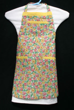 """White background with yellow and red flowerrs and green leaves child's apron with adjustable strap, allowing easy adjustment for fitting a child sized 4-6.  The apron grows with the child!  The apron has yellow binding across the top and on top of each of the three pockets. Made of woven cotton for easy cleaning The apron without straps is 18"""" long.  The waist is adjustable from 14"""" to 24""""."""