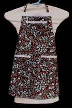 """Brown background with white and aqua flowers child's apron with adjustable strap, allowing easy adjustment for fitting a child sized 4-6.  The apron grows with the child!  The apron has white binding across the top and on top of each of the three pockets. Made of woven cotton for easy cleaning  The apron without straps is 18"""" long.  The waist is adjustable from 15"""" to 24""""."""