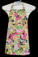 """White background with pink, yellow, green and grey flowers with accents of black child's apron with adjustable strap, allowing easy adjustment for fitting a child sized 4-6.  The apron grows with the child!  The apron has one pocket. Made of woven medium weight cotton for easy cleaning  The apron without straps is 18"""" long.  The waist is adjustable from 15"""" to 24""""."""