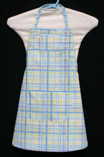 """White background with blue, purple, green & yellow plaid child's apron with adjustable strap, allowing easy adjustment for fitting a child sized 4-6.  The apron grows with the child!  The apron has two pockets. Made of woven medium weight cotton for easy cleaning  The apron without straps is 19"""" long.  The waist is adjustable from 15"""" to 24""""."""